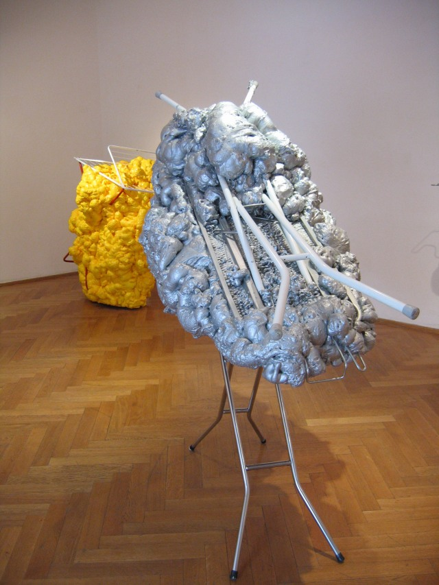 © Wilhelm Roseneder. Silberne Erweiterung/Silver expansion, 2006/2007. Austrian Cultural Forum. Bratislava, Slovakia 2007.  Bügelbrett, Styropor, Plastikflaschen, Klebeband, Verpackungsmaterial, Polyurethan, Lack/Ironing board, styropor, plastic bottles, sticky tape, packing materials, polyurethane, varnish, 1.40x1.50x90 cm. Gelbe Erweiterung/Yellow expansion, 2006/2007. Wäschetrockner, Styropor, Plastikflaschen, Klebeband, Verpackungsmaterial, Polyurethan, Lack/Airiel drier, styropor, plastic bottles, sticky tape, packing materials, polyurethane, varnish, 1.26x1.23x90 cm