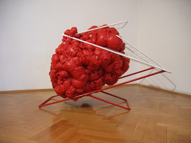 © Wilhelm Roseneder. Rote Erweiterung/Red expansion, 2005. Austrian Cultural Forum. Bratislava, Slovakia 2007. Polyurethan, verschiedene Materialien, Acryllack auf Metall (Wäschetrockner)/Polyurethane, various materials, acrylic varnish on metal (clothes-dryer), 95x1.10x90 cm